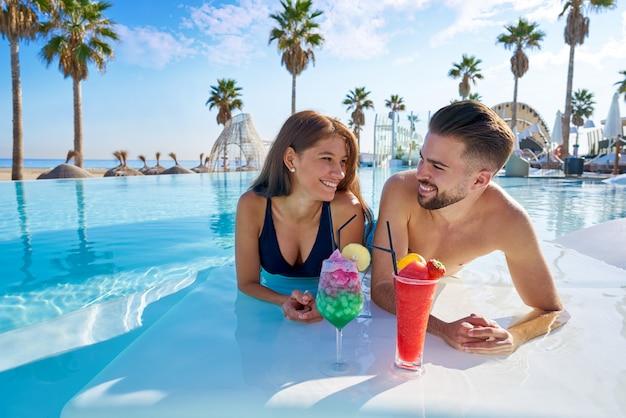 Junges paar auf infinity-pool-cocktails Premium Fotos