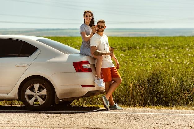 Junges paar, das an sonnigem tag auf dem auto reist Kostenlose Fotos