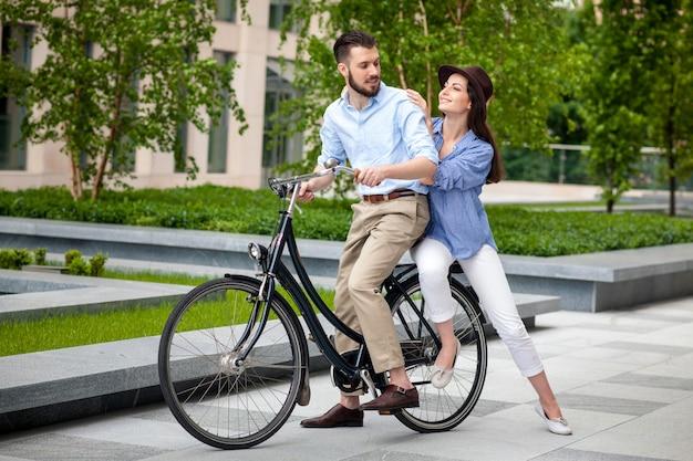 Junges paar, das auf einem fahrrad sitzt Kostenlose Fotos
