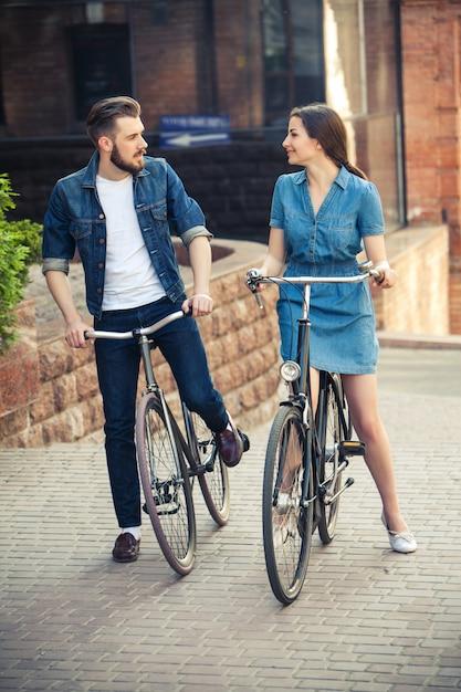 Junges paar, das auf fahrrad gegenüber stadt sitzt Kostenlose Fotos