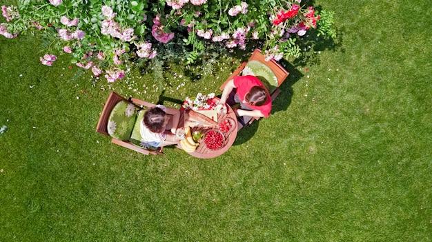 Junges paar, das essen und getränke im schönen rosengarten am romantischen datum genießt, luftansicht von oben von mann und frau, die zusammen draußen im park essen und trinken Premium Fotos