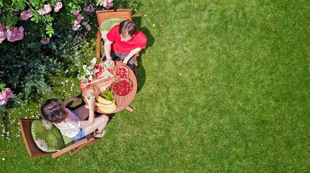 Junges paar, das essen und getränke im schönen rosengarten an einem romantischen datum genießt Premium Fotos