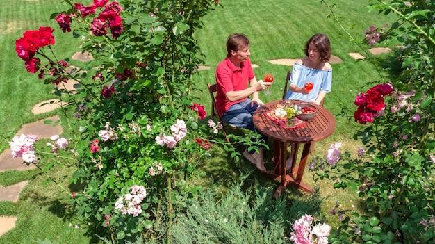 Junges paar, das essen und wein im schönen rosengarten am romantischen datum genießt, luftansicht von oben von mann und frau, die zusammen draußen im park essen und trinken Premium Fotos