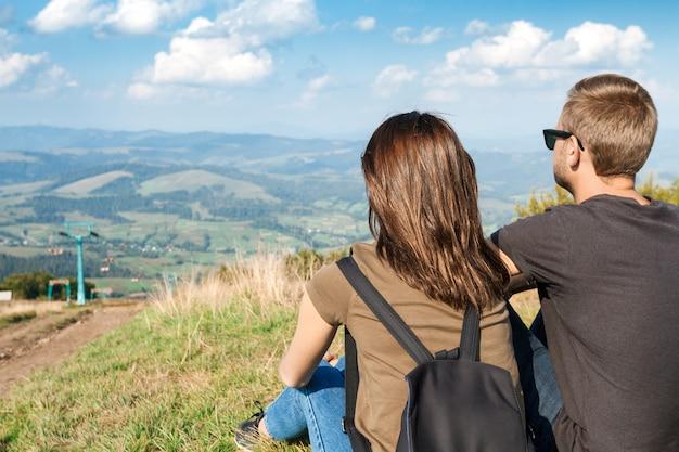 Junges paar, das gebirgslandschaft genießt, auf hügel sitzend Kostenlose Fotos