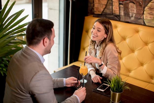 Junges paar, das im café sitzt und orangensaft trinkt Premium Fotos