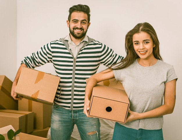 Junges paar, das kisten lächelt und hält, während es zwischen ausgepackten kisten steht Premium Fotos