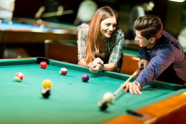 Junges paar, das pool in der bar spielt Premium Fotos