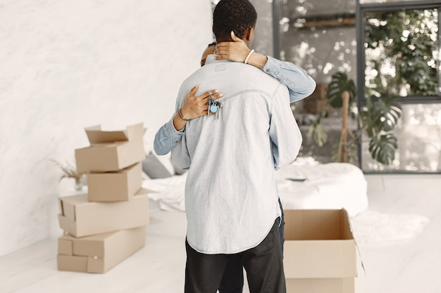 Junges paar, das zusammen in ein neues zuhause einzieht. afroamerikanerpaar mit pappkartons. frau hält schlüssel. Kostenlose Fotos