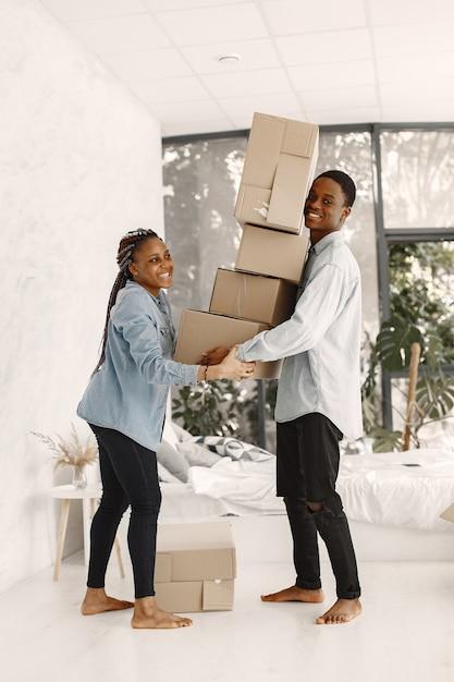 Junges paar, das zusammen in ein neues zuhause einzieht. afroamerikanerpaar mit pappkartons. Kostenlose Fotos