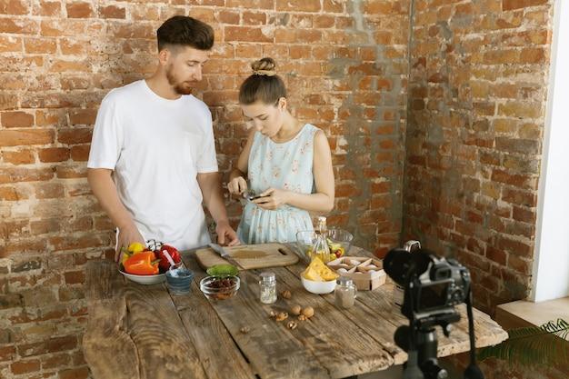 Junges paar, das zusammen kocht und live-video für vlog aufzeichnet Kostenlose Fotos