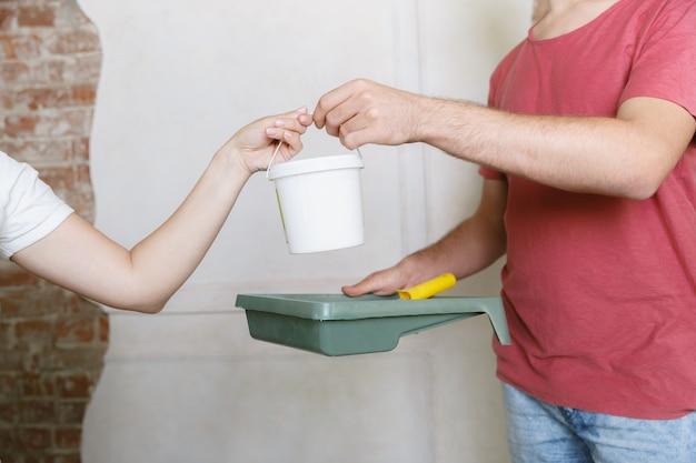 Junges paar, das zusammen wohnungsreparatur macht. verheirateter mann und frau machen renovierung oder renovierung. konzept der beziehungen, familie, liebe. die wand zusammen streichen und lachen. Kostenlose Fotos