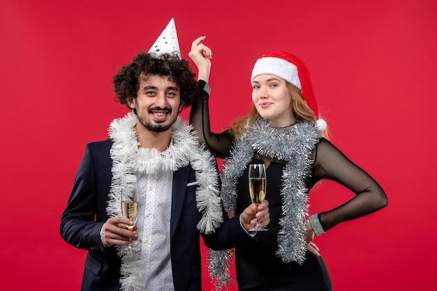 Junges paar der vorderansicht, das neues jahr auf weihnachtsliebe der roten wand feiert Kostenlose Fotos