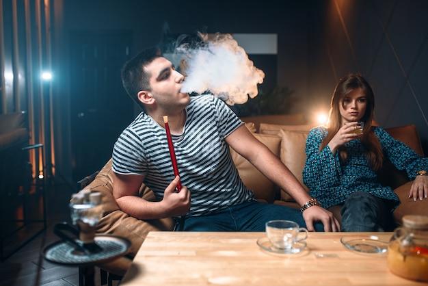 Junges paar entspannen und shisha rauchen Premium Fotos