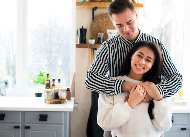 Junges paar in der küche sitzen und kuscheln Kostenlose Fotos