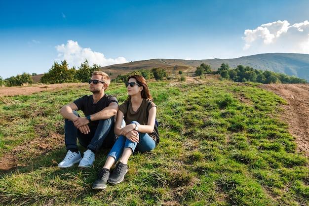 Junges paar lächelt, genießt berge lanscape, sitzt auf hügel Kostenlose Fotos
