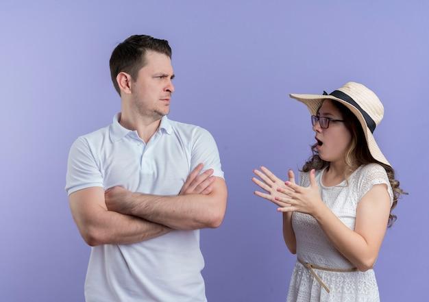 Junges paar mann und frau streiten frustrierte frau, die mit wütendem gesicht auf ihren freund schaut, während er stirnrunzelnd über blauer wand steht Kostenlose Fotos