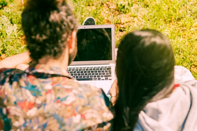 Junges paar mit laptop in lichtung Kostenlose Fotos