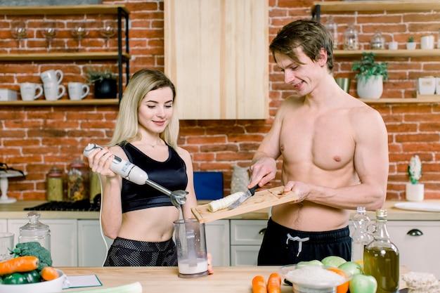 Junges paar mit stabmixer, der süßen milchshake-smoothie in der küche zu hause macht. milch nach dem training trinken. sporternährungsdiät nach dem fitnessstudio. gesunder lebensstil Premium Fotos