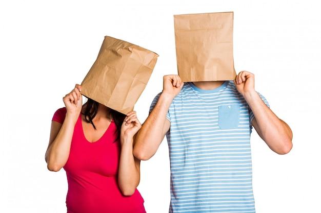 Junges paar mit taschen über köpfen Premium Fotos