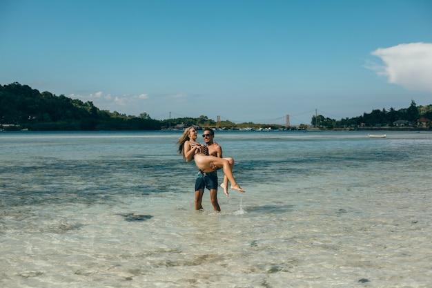 Junges paar posiert am strand, spaß im meer, lachen und lächeln Kostenlose Fotos