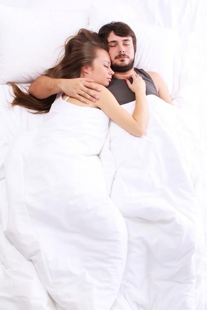 Junges paar schläft im bett Kostenlose Fotos