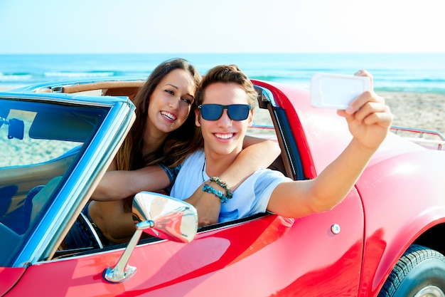 Junges paar selfie glücklich in res auto am strand Premium Fotos