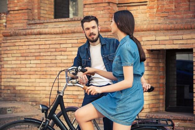 Junges paar sitzt auf einem fahrrad gegenüber der stadt Kostenlose Fotos