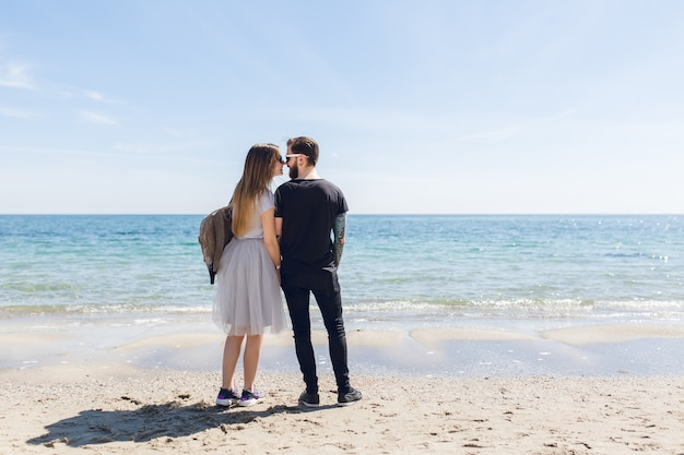 Junges paar steht am strand in der nähe des meeres Kostenlose Fotos
