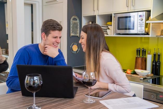 Junges paar sucht finanzielle dokumente in laptop am tisch im haus interieur. junge heimstudenten präsentieren e-learning-service Premium Fotos