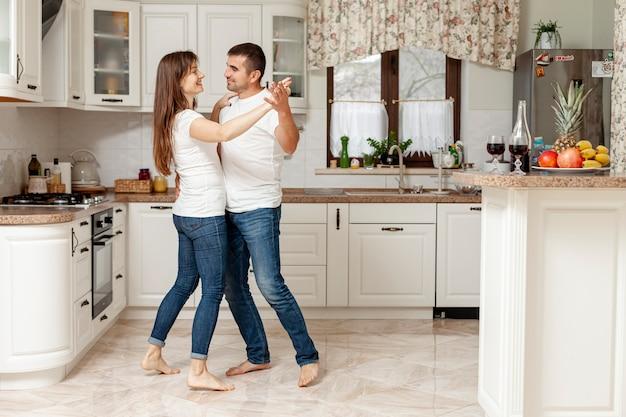 Junges paar tanzen in der küche Kostenlose Fotos