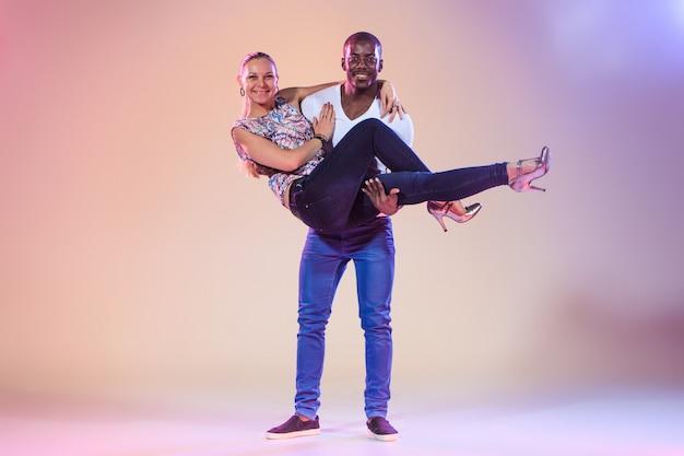 Junges paar tanzt soziale karibische salsa, studioaufnahme Kostenlose Fotos