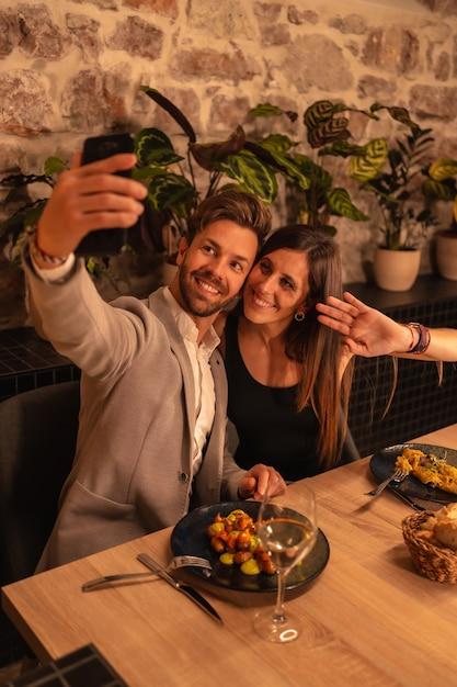 Junges paar verliebt in ein restaurant, spaß beim gemeinsamen essen haben, valentinstag feiern, ein souvenir-selfie machen. vertikales foto Premium Fotos