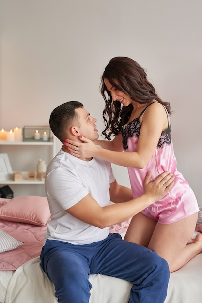 Junges paar verliebt in zu hause auf bett, das valentinstag feiert Premium Fotos