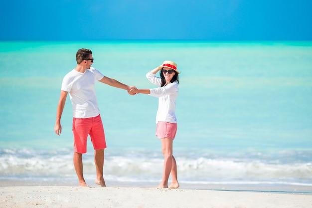 Junges paar zu fuß am tropischen strand Premium Fotos