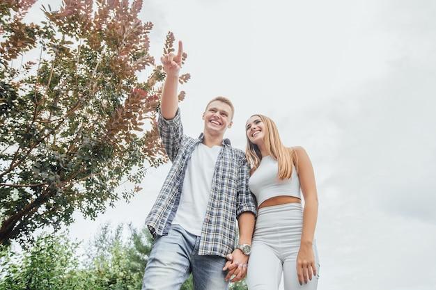 Junges paar zusammen im park. romantisches paar, das draußen geht. mann zeigt mädchen etwas Premium Fotos