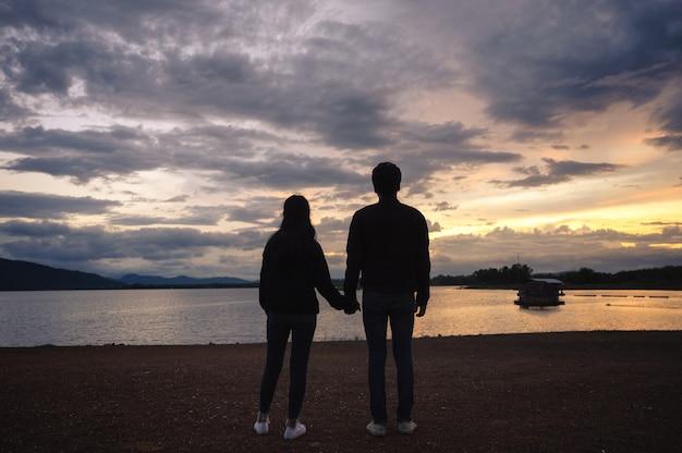 Junges paarhändchenhalten auf reservoir bei sonnenuntergang Premium Fotos