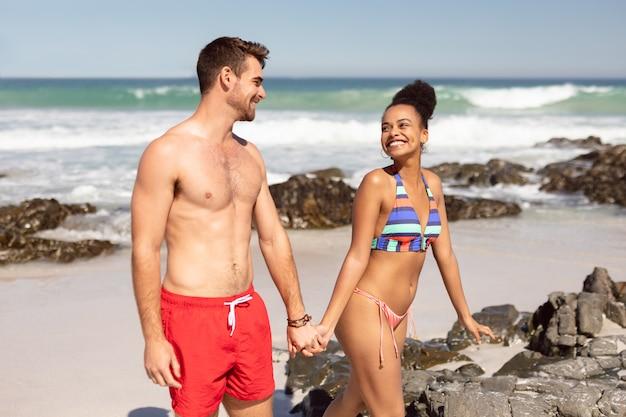 Junges paarhändchenhalten und gehen auf strand im sonnenschein Kostenlose Fotos