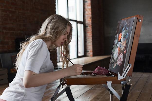 Junges recht blondes mädchen mit der bürste und palette, die nahe gestellzeichnungsbild in einem studio sitzen Premium Fotos