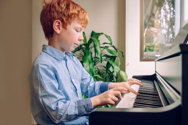 Junges rotes haarkind, das klavier spielt. kleiner junge, der zu hause musikunterricht auf einer tastatur einstudiert. musikkarriere-konzept studieren und lernen. familienlebensstil mit kindern. bildungsaktivitäten zu hause. Premium Fotos
