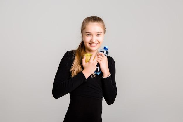 Junges schlankes mädchen hält einen apfel und eine flasche wasser. gesunder lebensstil Premium Fotos
