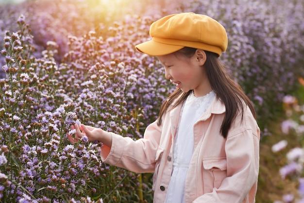 Junges schönes asiatisches mädchenkind, das blume beobachtet und im lila blumenfeld lächelt. Premium Fotos
