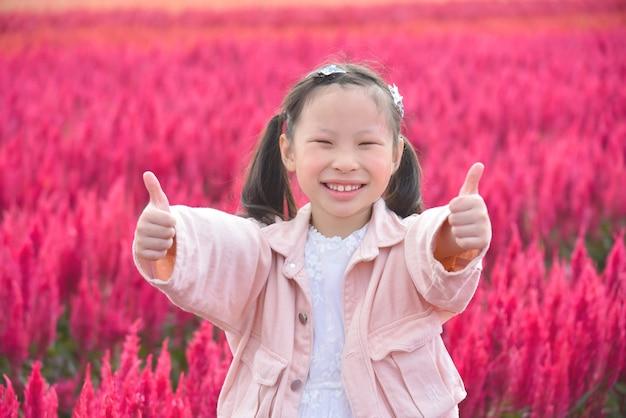 Junges schönes asiatisches mädchenkind, das lächelt und daumen oben im roten blumenfeld zeigt. Premium Fotos