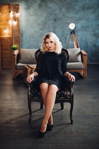 Junges schönes blondes mädchen, das im schwarzen kleid, in den hohen absätzen sitzen auf stuhl im luxusinnenraum und im betrachten der kamera trägt. heiße frau mit voluminösem haar und professionellem make-up. konzept der mode. Premium Fotos