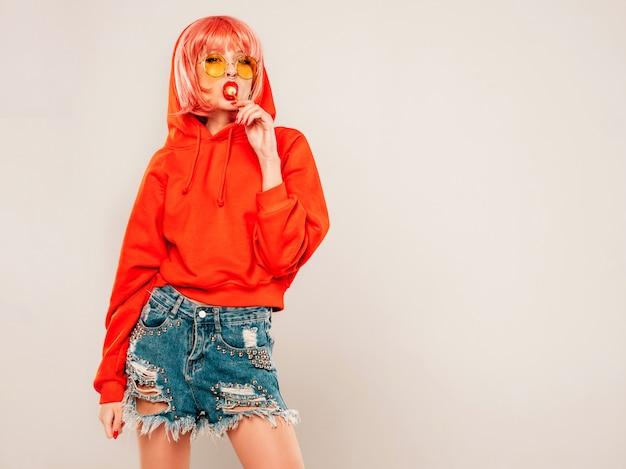 Junges schönes hipster böses mädchen im trendigen roten sommer roten kapuzenpulli und ohrring in ihrer nase. sexy sorglose frau, die im studio auf grauem hintergrund in perücke aufwirft. heißes modell leckt runde kandiszucker Kostenlose Fotos