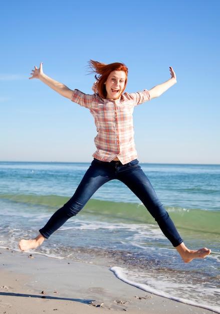 Junges schönes mädchen, das am strand springt. Premium Fotos