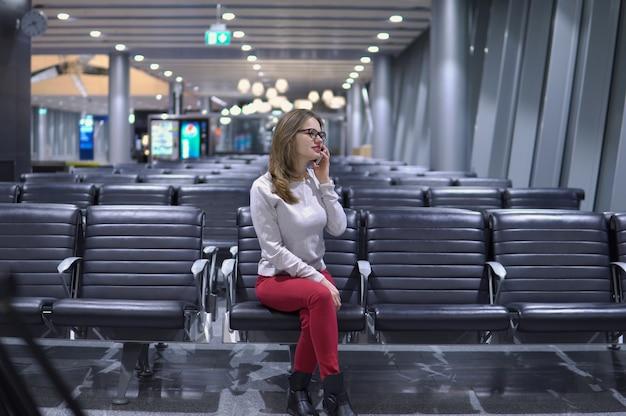 Junges, schönes mädchen, das am telefon in einem leeren flughafenterminal spricht Premium Fotos