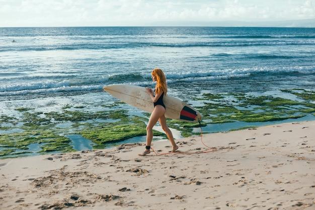 Junges schönes mädchen, das auf dem strand mit einem surfbrett, frauensurfer, meereswogen aufwirft Kostenlose Fotos
