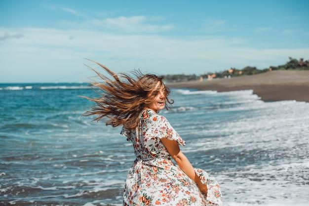 Junges schönes mädchen, das auf dem strand, ozean, wellen, heller sonne und gebräunter haut aufwirft Kostenlose Fotos
