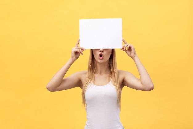Junges schönes mädchen, das ein leeres blatt papier lächelt und hält Premium Fotos