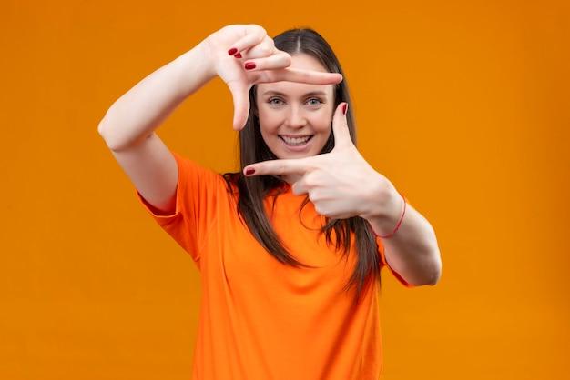 Junges schönes mädchen, das orange t-shirt trägt, das rahmen mit händen und fingern lächelt, die fröhlich über lokalisiertem orange hintergrund stehen Kostenlose Fotos